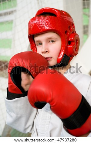 caucasian boy in red helmet and gloves making taekwondo punch into camera