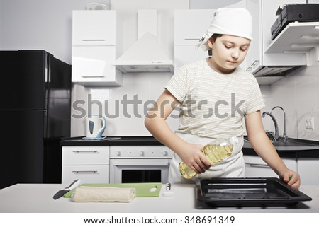 Caucasian boy pouring oil from bottle into pot while cooking at the kitchen - stock photo