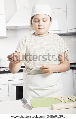 Caucasian boy stretching dough while cooking croissants at the kitchen - stock photo