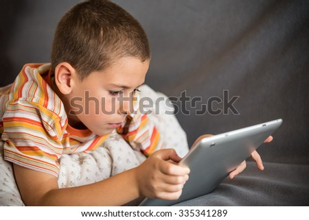 Caucasian boy using tablet, reading