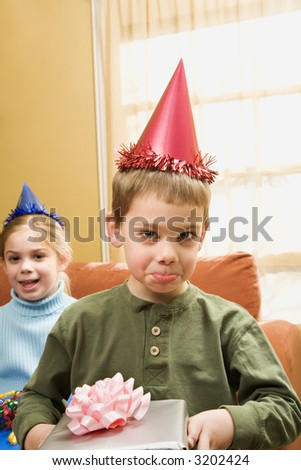 Caucasian boy wearing party hat pouting and looking at viewer. - stock photo