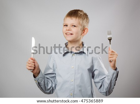 Caucasian boy with fork and knife. Hungry child.