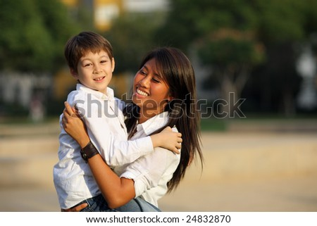 Caucasian boy with young adult asian girl outdoors. Shallow DOF. - stock photo