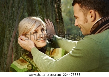 Caucasian boyfriend caressing happy romantic blond lady leaning against tree at forest, outdoor. Smiling. - stock photo