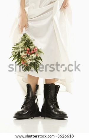 Caucasian bride holding bouquet down by her black combat boots. - stock photo