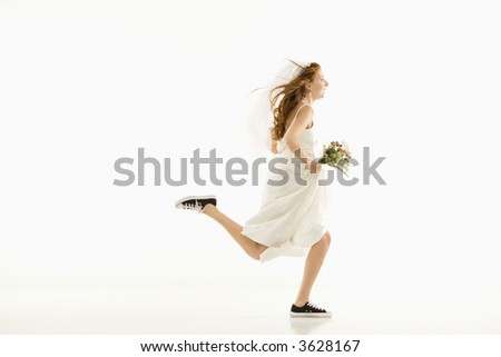 Caucasian bride running and holding bouquet. - stock photo