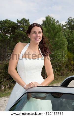Caucasian bride standing in car and smile to the camera