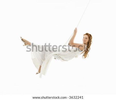 Caucasian bride swinging in swing set and looking at viewer. - stock photo