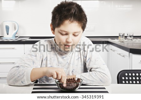 Caucasian brunette boy in pajama eating cereal bites from the bowl while sitting at kitchen table closeup - stock photo