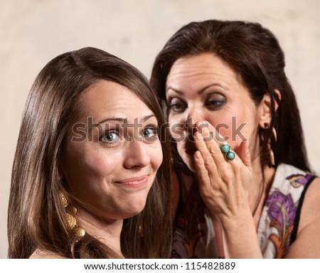 Caucasian brunette female listening to friend whispering - stock photo