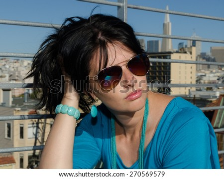 Caucasian brunette looking away with epic San Francisco cityscape on background - stock photo