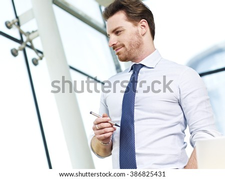 caucasian business executive looking out of window thinking in office. - stock photo