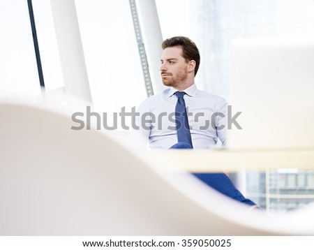 caucasian business executive sitting at desk looking away and thinking in modern office. - stock photo