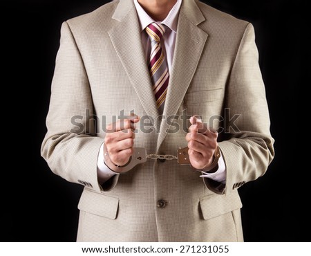 Caucasian business executive wearing a light brown suit and maroon tie in handcuffs. Corrupt businessman is arrested and handcuffed for corporate scam and fraud.  - stock photo
