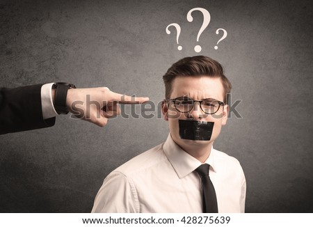 Caucasian business hand pointing at scared employee with big white question marks above his head - stock photo