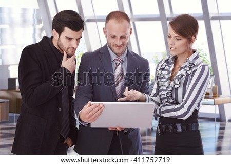 Caucasian business people looking at laptop computer screen at office. Bristly businessmen in suit and businesswoman pointing at screen. Standing. - stock photo