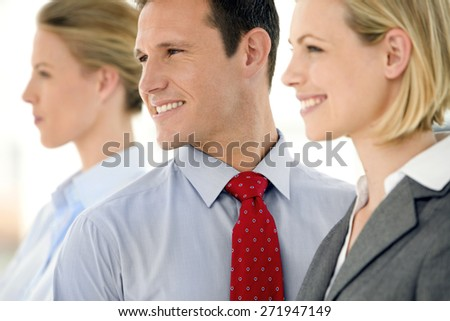 Caucasian business team portrait. Three young business partners standing in a row. All looking away. - stock photo