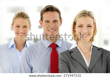 Caucasian business team portrait. Three young business partners standing in a row. All looking to the camera. - stock photo