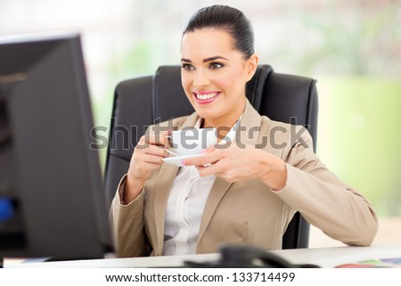 caucasian business woman having tea in front of computer - stock photo