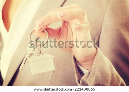 Caucasian business woman holds silver home keys. - stock photo