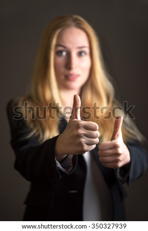 Caucasian business woman in casual suit giving thumb up gesture over gray background. - stock photo