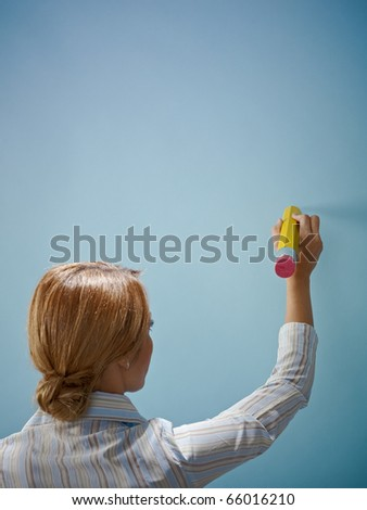 caucasian business woman writing a message on blue wall. Vertical shape, rear view, copy space - stock photo