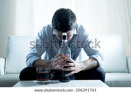 caucasian businessman alcoholic wearing a blue work shirt and loose tie drunk and drinking  Scotch or Whisky sitting on a sofa at home after a long day or week of work on a white background.  - stock photo