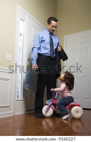 Caucasian businessman at door with briefcase with daughter looking up at him. - stock photo