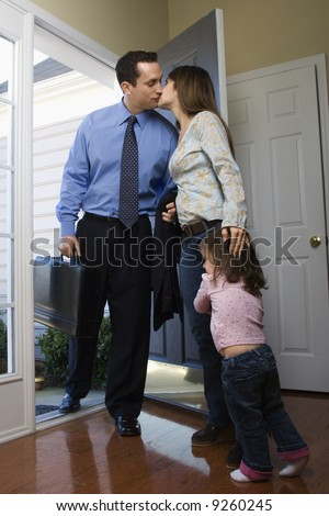 Caucasian businessman   at open door kissing wife while daughter hugs her leg. - stock photo