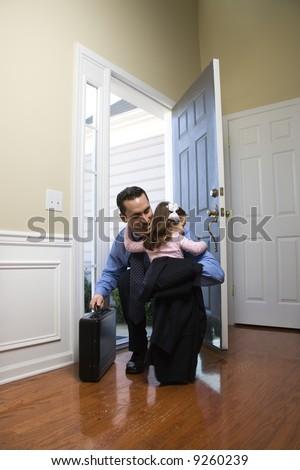 Caucasian businessman   at open door with briefcase hugging daughter. - stock photo