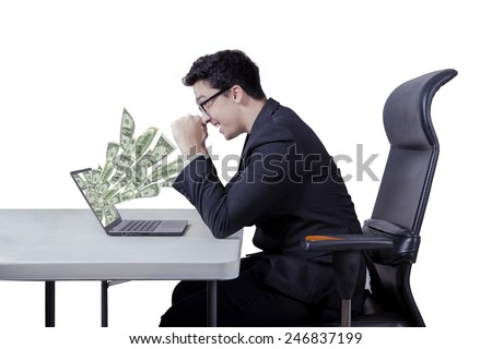 Caucasian businessman celebrate his success while looking at money dollars from laptop - stock photo