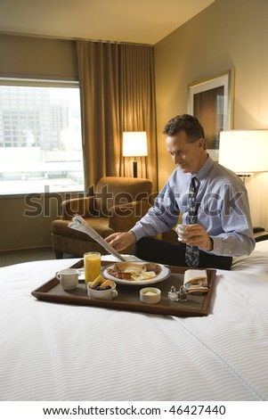 Caucasian businessman enjoys his breakfast while reading the morning paper. He is sitting on the bed and holding a cup of coffee. Vertical shot.