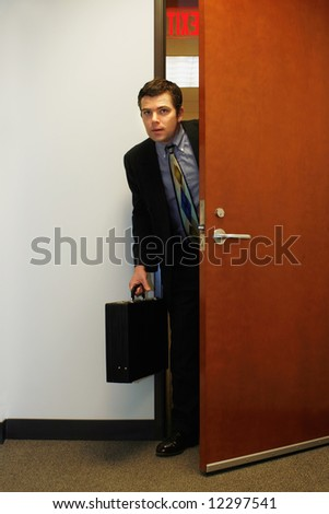 Caucasian businessman furtively peeking through a doorway - stock photo