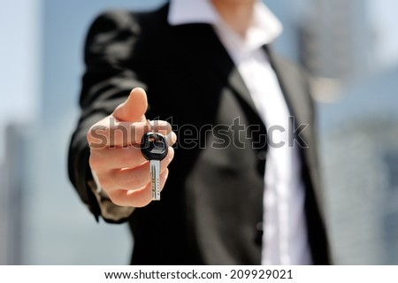 caucasian businessman holding a car key in his hand - new car buy sale concept - stock photo