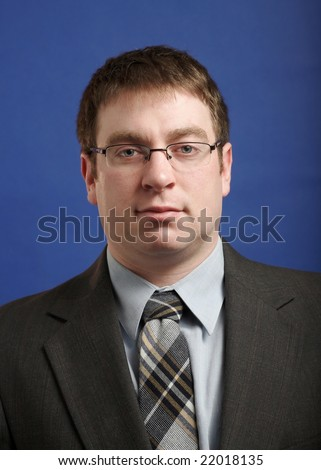 Caucasian businessman in suit on blue background - stock photo