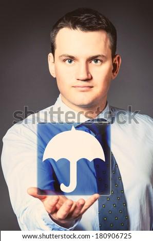 caucasian businessman is holding umbrella symbol in hands - stock photo
