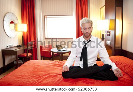 Caucasian businessman meditating in bed in lotus position. - stock photo
