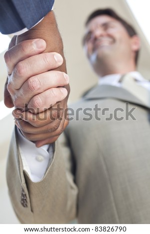 Caucasian businessman or man shaking hands with an African American colleague doing a business deal - stock photo