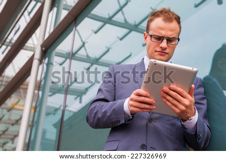 Caucasian businessman outside office using white tablet pc on a office block background. Copy space. - stock photo