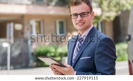 Caucasian businessman outside office using white tablet pc on a office block background. Copy space.