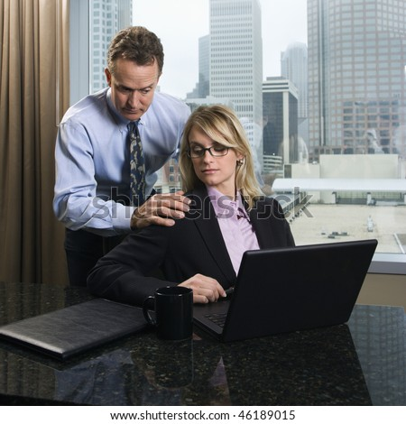 Caucasian businessman puts his hands on a businesswoman's shoulders as she gives an annoyed look. They are in the office and the city can be seen in the background. Square shot. - stock photo