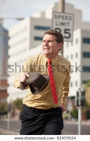 Caucasian businessman runs on the streets to make it to meeting on time - stock photo