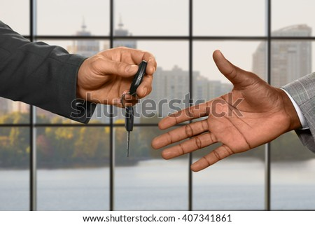 Caucasian businessman's hand giving key. Passing car keys at daytime. What's mine is yours. Say no to public transport. - stock photo