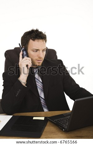 Caucasian businessman sitting at a desk while talking on the telephone