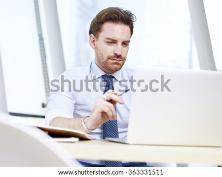 caucasian businessman sitting at desk looking at laptop screen and thinking in office. - stock photo
