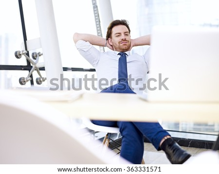 caucasian businessman sitting at desk looking blankly at laptop screen in office.