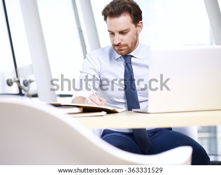 caucasian businessman sitting at desk taking notes while using laptop computer in office. - stock photo