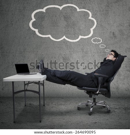 Caucasian businessman sitting on armchair while looking at cloud tag of his dreams - stock photo