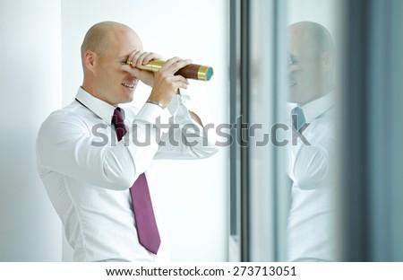 caucasian businessman spying using telescope thru office window - stock photo