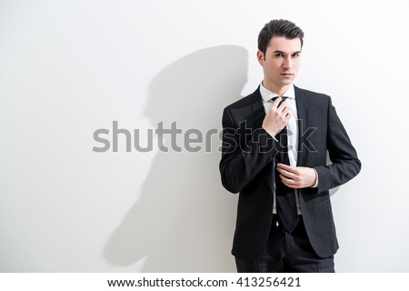 Caucasian businessman standing against white wall with shadow and adjusting tie - stock photo